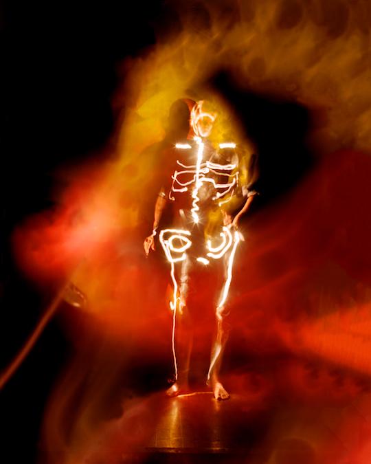 Eine Wolke aus rotem und orangefarbenem Licht. Fast bildfüllend groß vor schwarzem Hintergrund. In der Mitte der wie augenförmig wirkenden Farbwolke ein schwarzer Kreis, fast wie eine Iris. Davor, kleiner, steht ein menschliches Skelett aus weißem Licht. Ein helles Knochengerüst. Hinter ihm der Schatten einer menschlichen Gestalt geworfen auf die augenförmig schwebenden Farben.