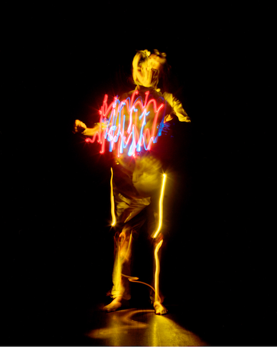 A photograph by Pete Eckert: A bright yellow figure in the middle of black, vaguely resembling a human body. The left arm seems to be cut in the middle, the right hand is stretched out as a fist. Head and face are barely recognizable, made out of yellow lightstreaks. In front of the upper body, in the hight of the heart, there are bright red and blue vibrant lines, resembling those of an oscillograph. Along the legs very bright yellow vertical lines as if this light would origin from the bones in the legs.