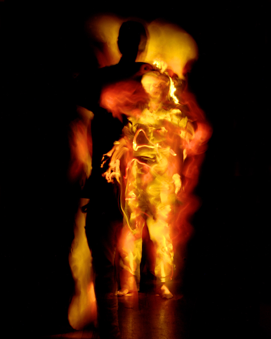 A photograph by Pete Eckert: Fiery orange-yellow streaks glowing out of the black. In the foreground stands a figure of vaguely human shape whose definitions are hard to make out, a strange head over a robe made out of lightstreaks. Only the left hand and the bare feet resemble cleary those of human bodies. Behind the figure a huge black shadow, dark and sharply carved out of the fiery lights. It is much taller than the figure who seems to cast it, towering over it.